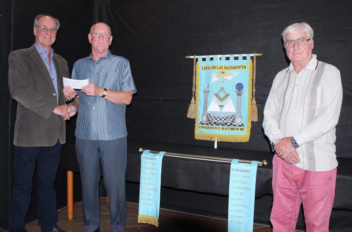 Past Worshipful Master, Brian McArdle, making the presentation to the President of Reach Out, Brian Procter, in the presence of Charity Steward, Vernon Sayce.