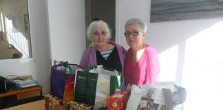 Pictured with some of the food for distribution are Help at Home volunteers Eileen Mayes (left) and Sheila Rowell.