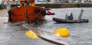 Rain and gales made it difficult for the scuttled sunken submarine to be brought into port by police.