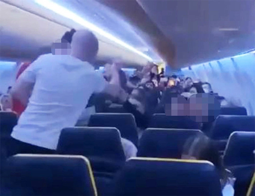 A fight appeared to break out between four males - with an alleged punch thrown - while a female passenger stands between them.