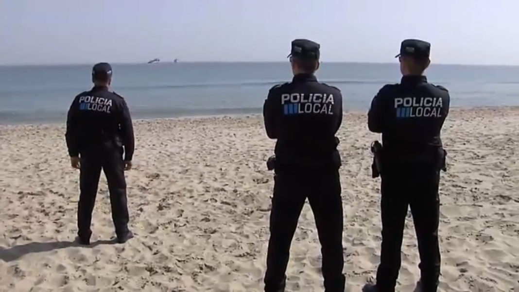Police watching the search and rscue operation from La Manga beach