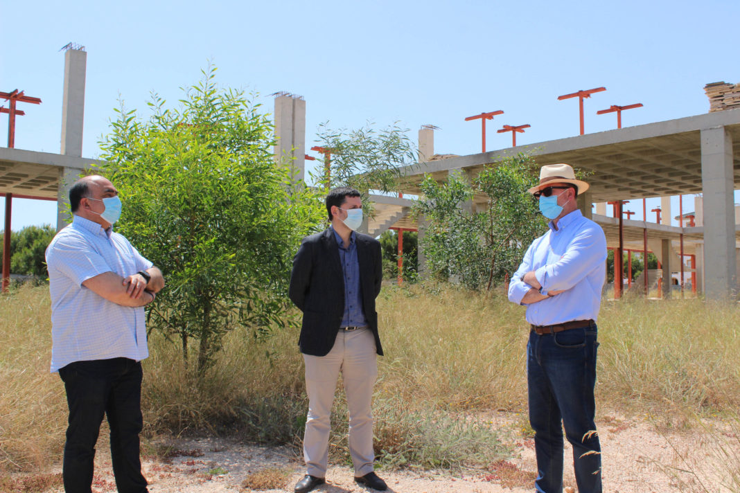 The mayor with the contractor and councillor for the coast inspect the abandoned building prior to restarting construction