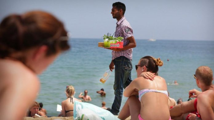The Mojiteros concoct their drinks - with various fruits and additives - and hide them away from view of the Policia