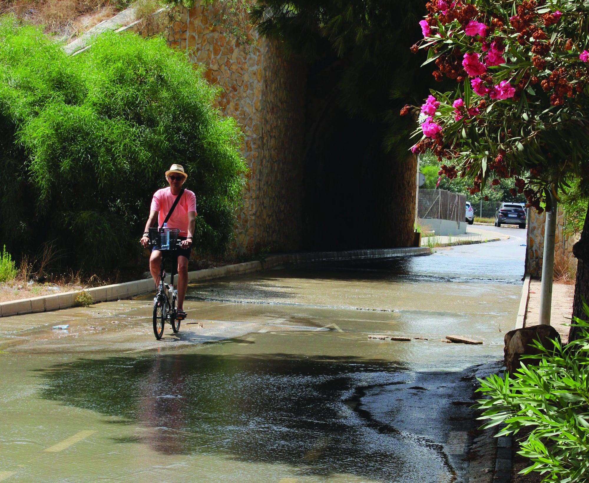 A cyclist pedalling through the sewage in La Zenia Village