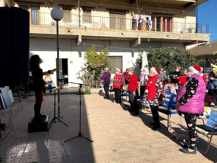 Crescendo Choir members singing Christmas Carols outside Rincon de Miguel Restaurant,