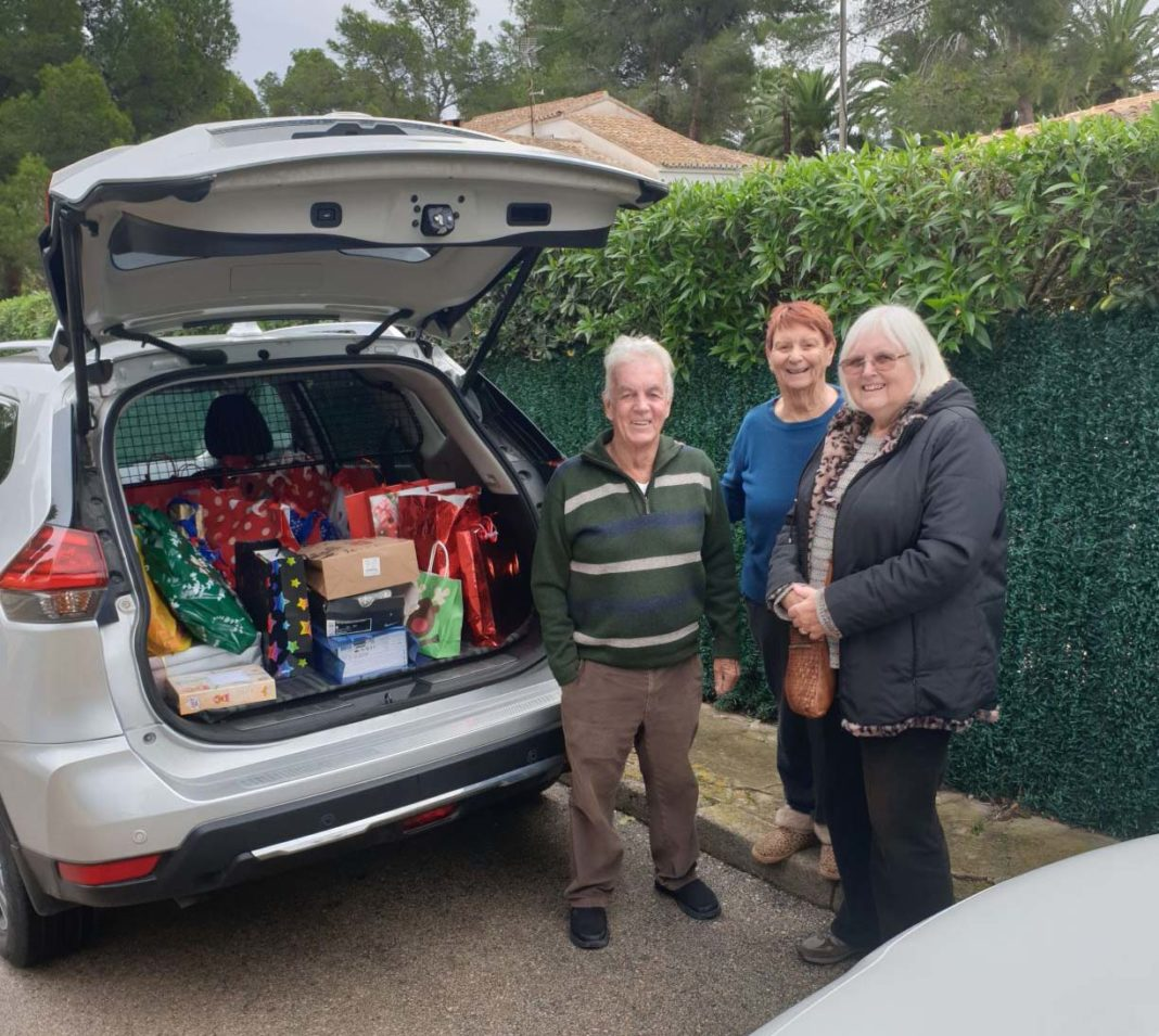 Local Freemasons help the  Red Cross distribute presents to needy children.