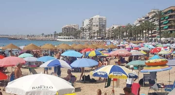 Playa de la Cura Torrevieja bustling with sunbathers.