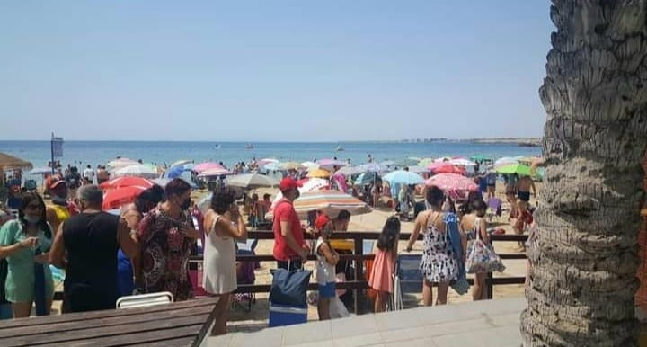 Queues form to await entry to the beach.