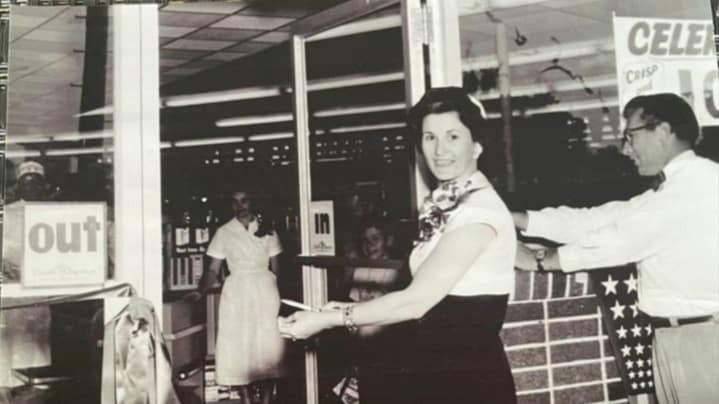 Mildred Shaddock cuts the ribbon opening Shaddock's Rainbow Supermarket in Lake Jackson, Texas.